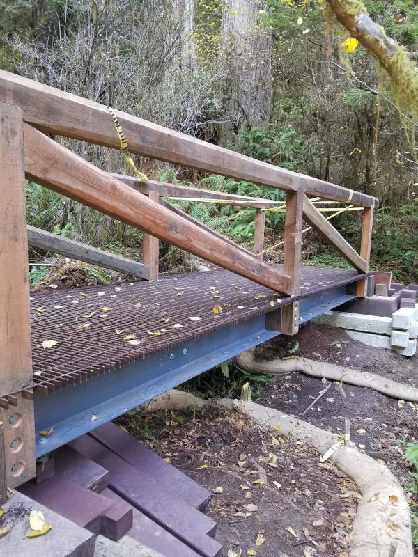 Bridge built f fiberglss girders, p[lastic beams, metal grating and redwood guardrails installed over a seasonal creek