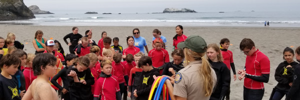 California State Parks ranger holding hula hoops in front of thirty young people in wetsuits. The leader is holding a training for North Coast Junior Lifeguard students on Trinidad State Beach