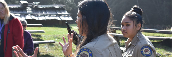 Two young women in California State Park Uniforms speaking to visitors at Sumeg Village in Patrick's Point State Park